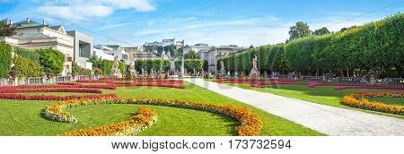 Panoramic View Of Famous Mirabell Gardens With The Old Historic Fortress Hohensalzburg In The Backgr