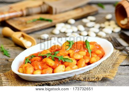 Homemade beans stew on a plate and on old wooden table. White beans stewed with carrots and tomato sauce and served with green arugula. Delicious and hearty beans side dish. Rustic style. Closeup