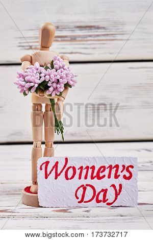 Wooden man with bouquet. Greeting for dear women.