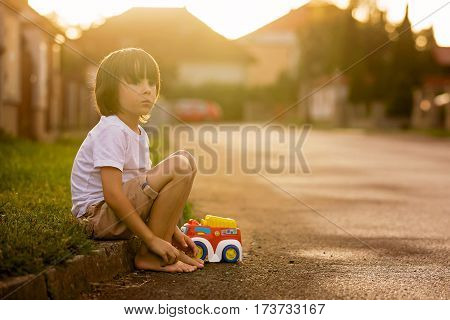 Cute Sweet Child, Boy, Playing With Car Toys On The Street In Village On Sunset