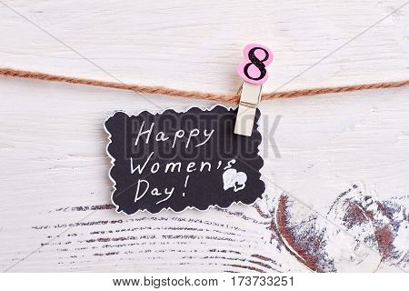 Greeting card on wooden surface. Laconic congratulation for woman.