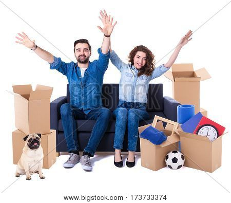 Moving Day And New Home Concept - Cheerful Couple Sitting On Sofa With Brown Cardboard Boxes And Dog