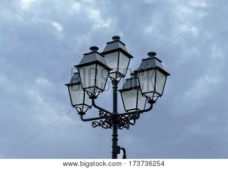 Old big street lamppost with cloudy sky
