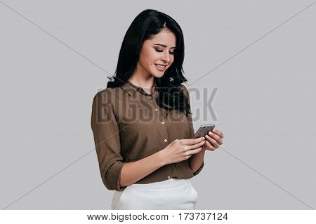 Woman with smart phone. Attractive young woman in smart casual wear using smart phone and smiling while standing against grey background