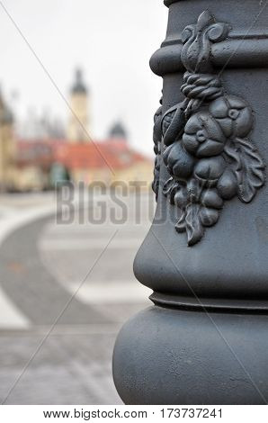 Metal decorative detail of a lamppost close up on blurred background of the old town. Bialystok, Poland.