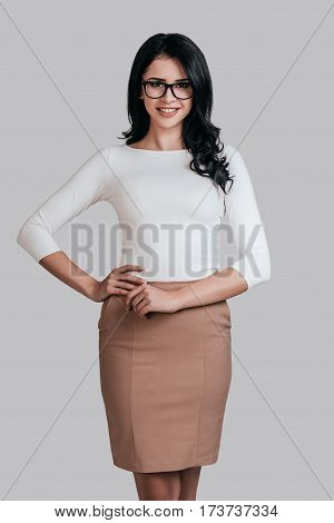 Modern businesswoman. Beautiful young woman in smart casual wear keeping hand on hip and smiling while standing against grey background