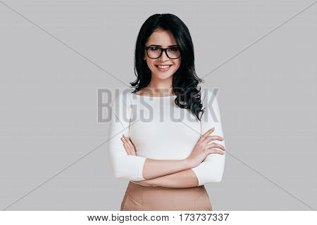 Confident business expert. Beautiful young woman in smart casual wear keeping arms crossed and smiling while standing against grey background