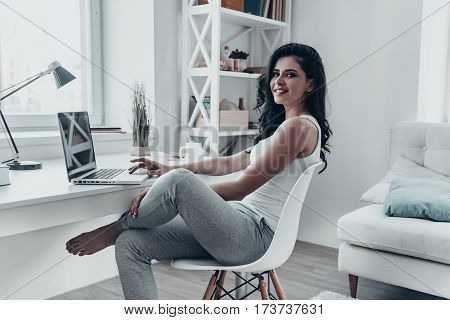 Surfing the net at home. Beautiful young woman using laptop and looking at camera with smile while sitting at the desk at home