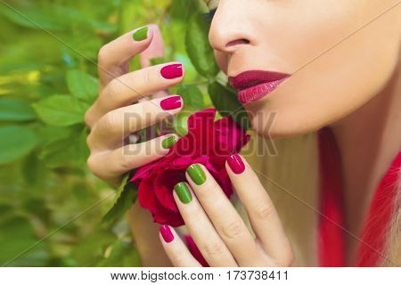 Trendy red green blue manicure and makeup on the girl with the rose in hand.