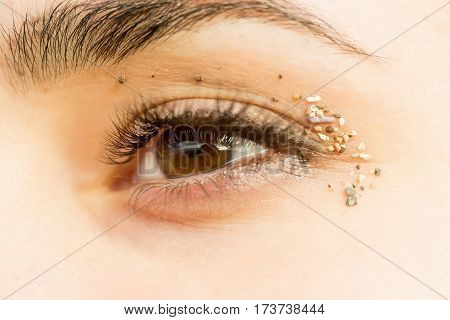 Pretty female eye brown color look with eyelashes and eyebrow natural granular sand on eyelids on young skin background
