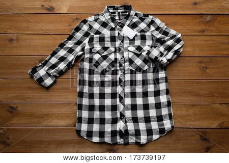 clothes, fashion and objects concept - checkered shirt with price tag on wooden background