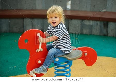 Cute Happy Baby Boy Riding Red Spring Rider
