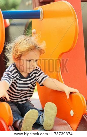 Cute Happy Baby Boy Riding From Orange Slide Board