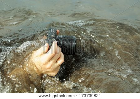 Black wet photo or video camera with lens in female hands filming under sea or ocean water on grey surface background