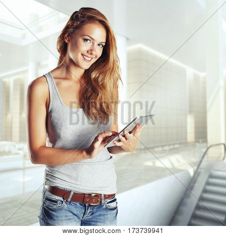 Woman holding tablet computer in hall shoping center. Working on touching screen