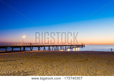 People walking on Glenelg Jetty at sunet South Australia