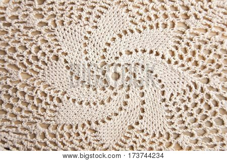 Knitted homemade white lace doily with a star pattern.