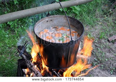 The process of cooking in the campaign. Metal bucket of fish soup on the fire.
