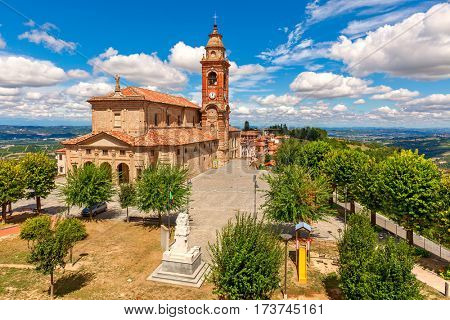 Parish church on town square under beautiful blue sky with white clouds surrounded by green trees  in small town of Diano d'Alba in Piedmont, Northern Italy.
