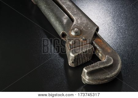 Old Pipe Wrench On A Black Surface.