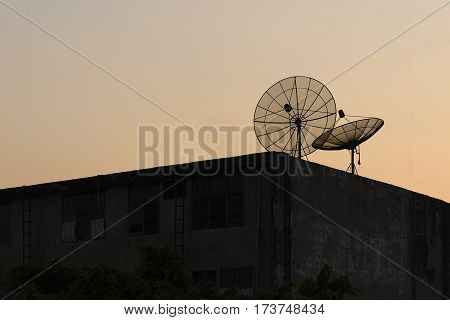 The TV satellite on the top of building with the silhouette scene