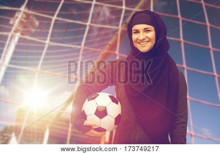 sport, football and people concept - happy muslim woman in hijab with soccer ball over goal background