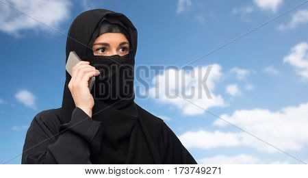 technology, communication and people concept - muslim woman in hijab calling on smartphone over blue sky and clouds background