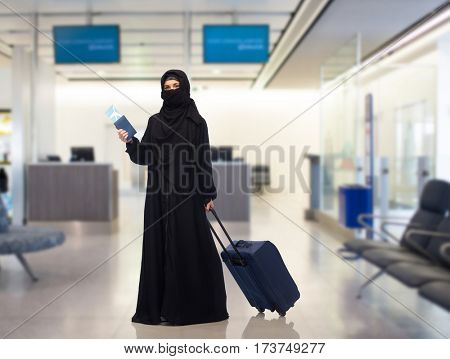 travel, tourism, flight and people concept - muslim woman in hijab with airplane ticket, passport and carry-on bag over airport waiting room background