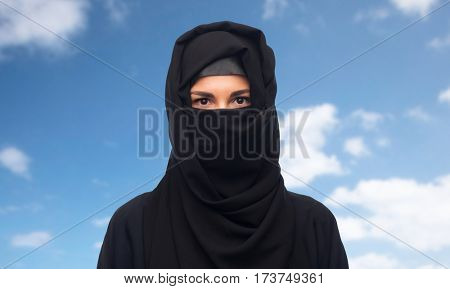 religious and people concept - muslim woman in hijab over blue sky and clouds background