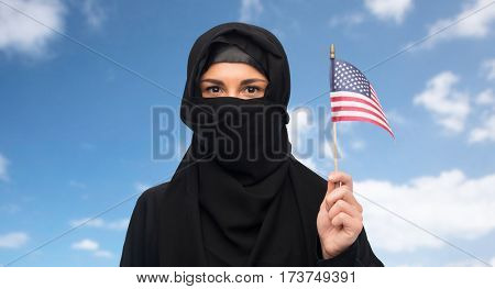 immigration and people concept - muslim woman in hijab with american flag over blue sky and clouds background
