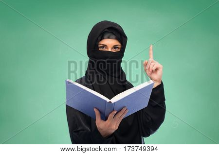 religion, education and people concept - muslim woman in hijab with book pointing finger up over green chalkboard background