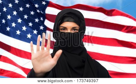 gesture, immigration, religious prohibition and people concept - muslim woman in hijab showing stop sign over american flag background