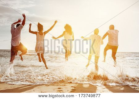 Happy family or friends at the beach running and jumping in the sunset sea. Friendship or vacations concept