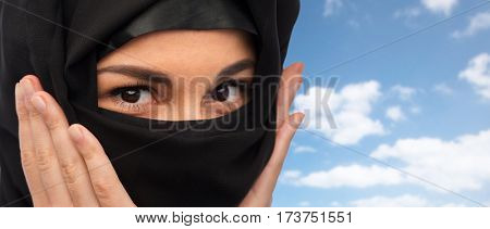 religious and people concept - close up of muslim woman in hijab over blue sky and clouds background