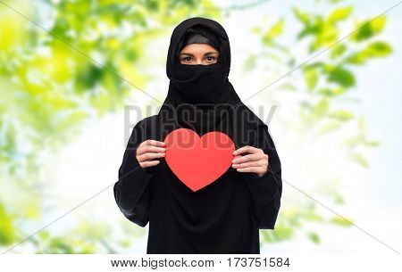 love, charity, valentines day and people concept - muslim woman in hijab holding red heart over green natural background