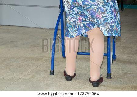 An elderly person with a blue walker