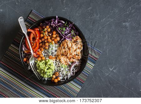 Grilled chicken rice spicy chickpeas avocado mash cabbage pepper buddha bowl on dark background top view. Delicious balanced food concept