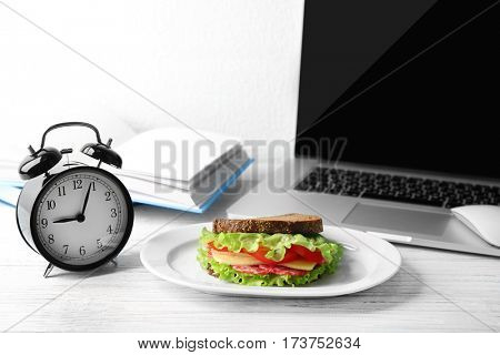 Plate with sandwich and alarm clock on wooden table