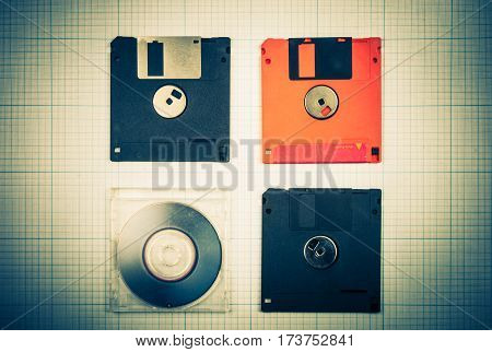 vintage background - computer floppy disks and mini-CD on the blueprint paper, toned