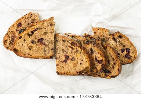 Slices of malt bread handmade with nuts, raisins and cranberries on white background