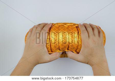 Thai silk Pumkin Pillow and hand on white background