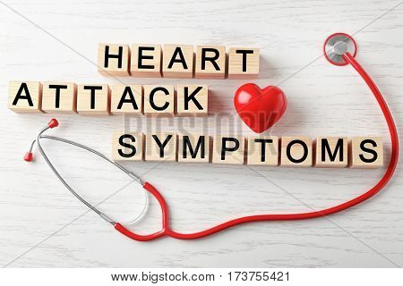 Text HEART ATTACK SYMPTOMS made of cubes and stethoscope on wooden background