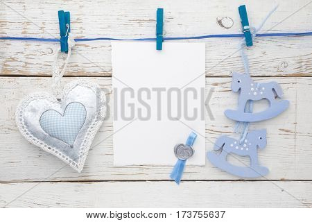 vintage rocking horse, fabric heart and empty card for adding text hanging on the rope on wooden floor