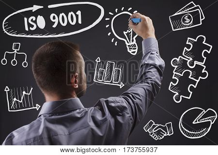 Technology, Internet, Business And Marketing. Young Business Man Writing Word: Iso 9001