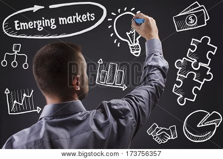 Technology, Internet, Business And Marketing. Young Business Man Writing Word: Emerging Markets