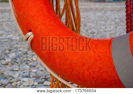 orange lifebuoy on a pebbly sea beach, sunset