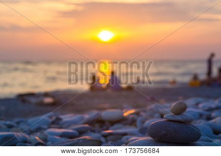 a couple and folded pyramid Zen pebble stones on the sea beach at sunset