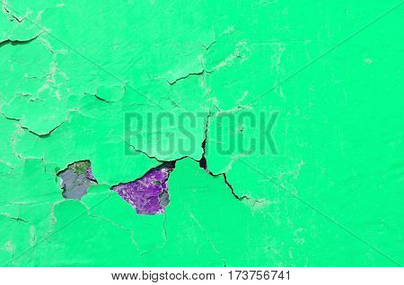 Peeling paint of green and purple colors on the stone texture background -closeup of texture peeling paint on the texture stone surface. Texture background with chipped peeling paint
