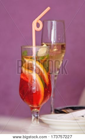 single glass transparent wine glass with a cocktail, slices of lemon and a straw, the second with champagne on a pink background