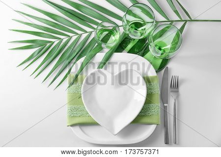Beautiful romantic table setting with green leaf